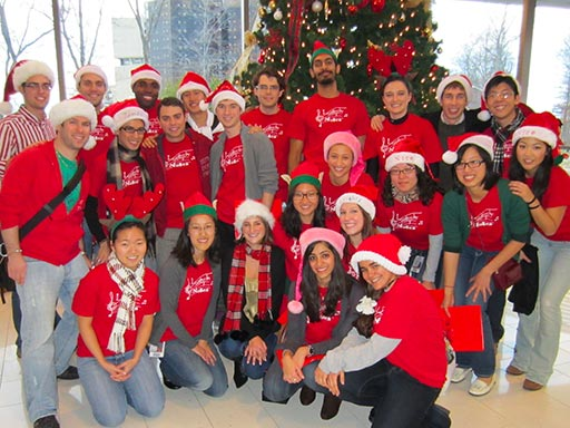 Students wearing red beside Christmas tree
